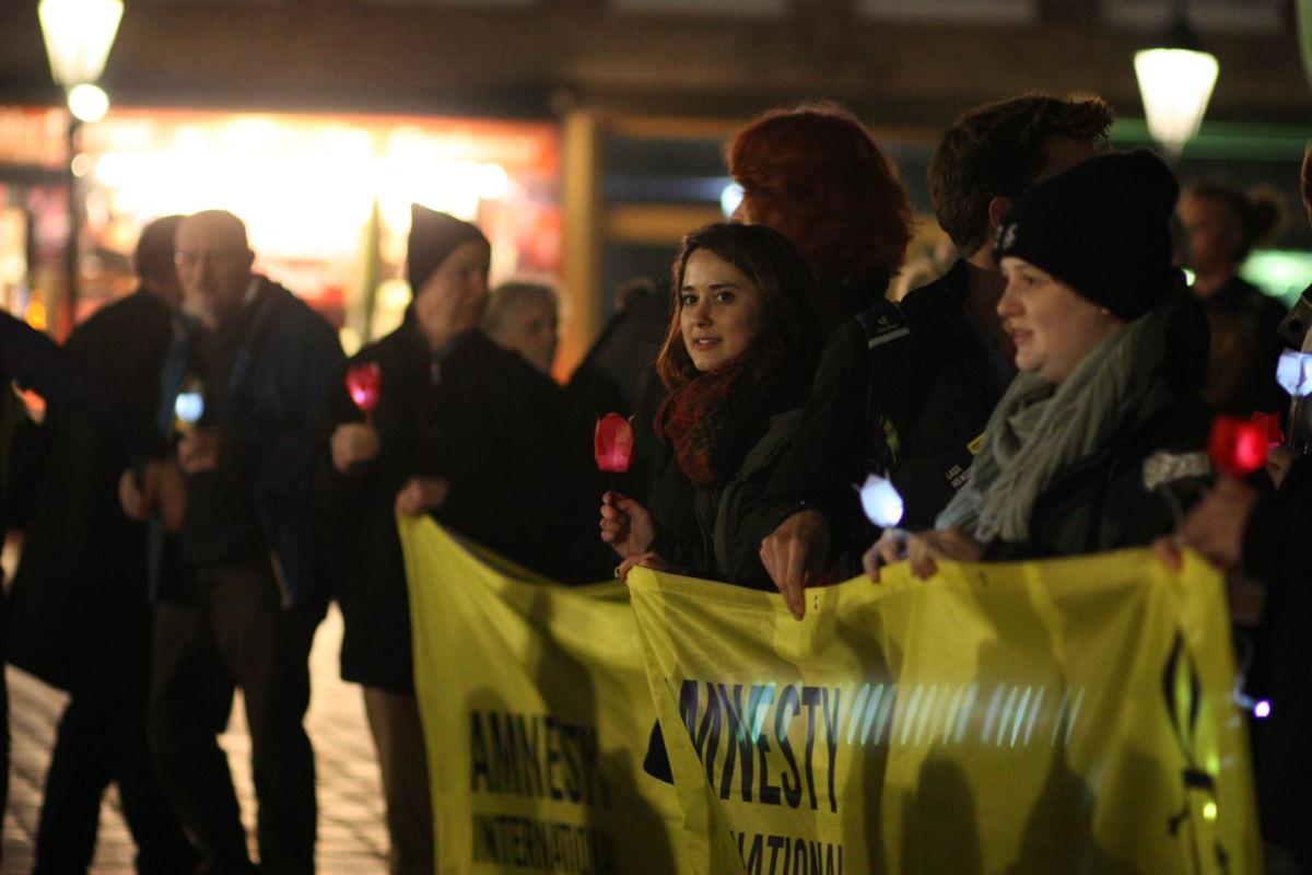 Menschen stehen zusammen bei einer Kundgebung mit einem Amnesty-Banner